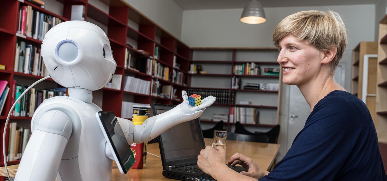 A white robot hands OFAI researcher Stephanie Gross a Rubik's cube